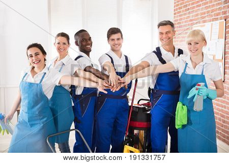 Portrait Of Happy Diverse Janitors In The Office With Cleaning Equipments Stacking Hands