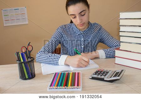 Sad schoolgirl with sitting with stack of books. Girl studying. Thoughtful young Girl sitting at desk
