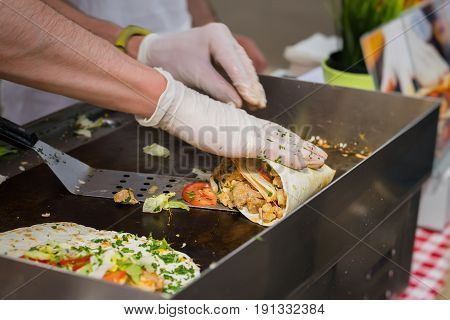 Close-up of hands of cook in latex gloves preparing fajitas or fajitos in park. Healthy fresh tortillas with grilled chicken fillet, avocado, fresh salsa, selective focus