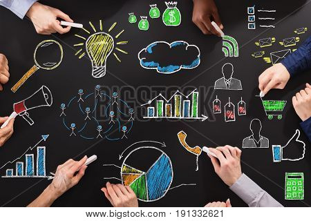 Overhead View Of Hands Drawing Business Strategy With Chalk On Blackboard