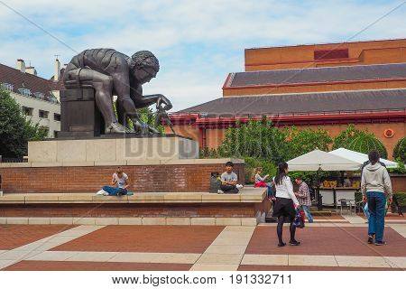 LONDON UK - MAY 27 2017: Outside view of the British Library building national library of the UK and its concourse with the Isaac Newton sculpture by Eduardo Paolozzi and the visitors sitting and passing by.