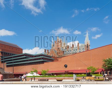 Outside view of the British Library building, national library of the UK in London, with the gothic towers of St Pancras Station behind the wall and the visitors sitting and passing by.