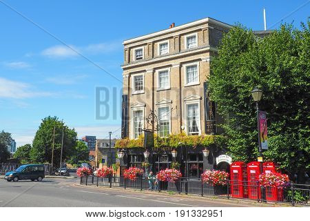 LONDON UK - 9TH AUGUST 2015: The outside view of the Mitre Hotel and Pub in Greenwich London in the sunny summer day with unidentified people passing by and the red telephone boxes standing nearby.