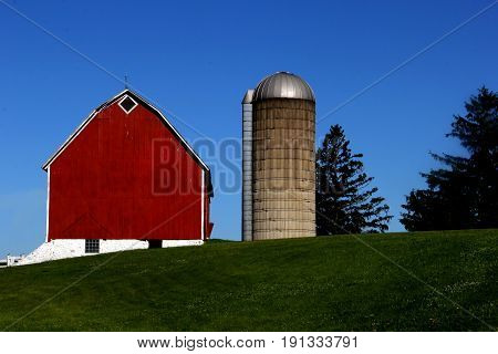 Old vintage wooden red barn and silo with a blue sky background