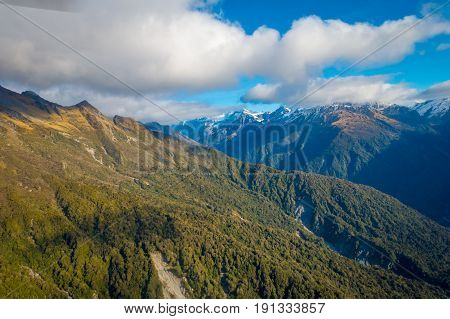 Beautiful landscape of the New Zealand - hills covered by green grass with mighty mountains covered by snow behind, South Island in New Zealand.