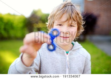 Cute school boy playing with colorful fidget spinner on the playground. Popular stress-relieving toy for school kids and adults.