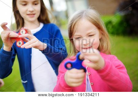 Two Funny Sisters Playing With Fidget Spinners On The Playground. Popular Stress-relieving Toy For S