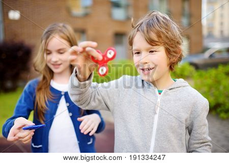 Two Funny Friends Playing With Fidget Spinners On The Playground. Popular Stress-relieving Toy For S