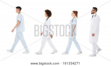 Multiracial Medical Team Walking In Row In Front Of White Background