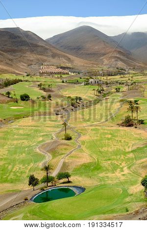 View on the green field for golf between the mountains a beautiful whte cloud and blue sky on the Canary Island Fuerteventura Spain.