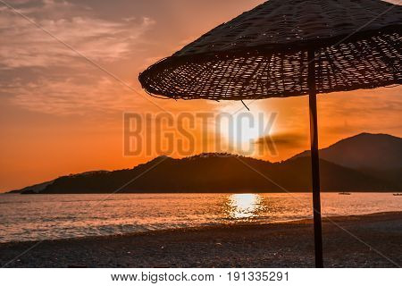 Sea side beach sunset and umbrella silhouette.