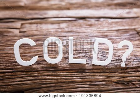 Close-up Of A Cold Text With Question Mark Sign On Wooden Background