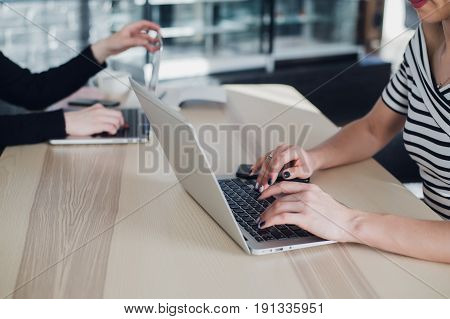 Close up shot of female workers in office writing information. Two ladies are sitting at a table and typing on laptops