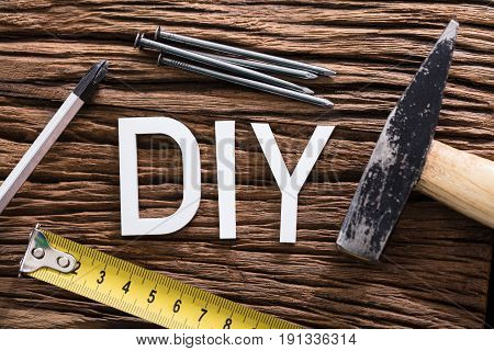 High Angle View Of DIY Text With Worktools On Wooden Table