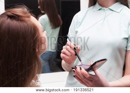 Make up artist applying make-up on girl face