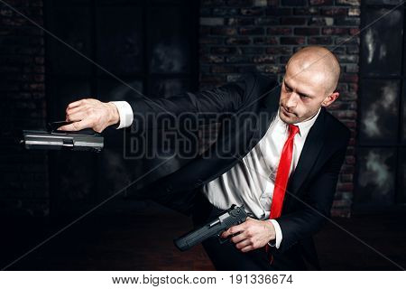 Serious killer shoot a pistols with two hands