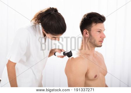 Close-up Of A Female Doctor Examining Skin Of Male Patient With Dermatoscope