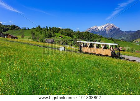 Stans, Switzerland - 8 May, 2016: people in a railroad car of the Stanserhornbahn railway,  Mt. Pilatus in the background. Stanserhornbahn is a funicular railway from the town of Stans to Mt. Stanserhorn in Switzerland.