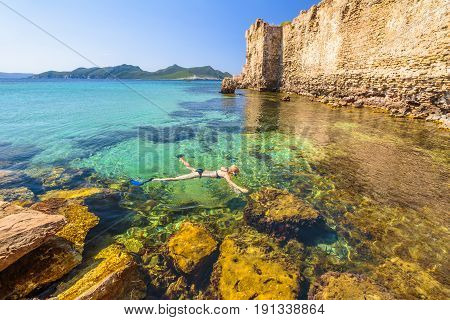 Woman bikini snorkeling in the rocks around Methoni Castle, a medieval fortification in Methoni port, Messenia, Peloponnese, Greece. Female snorkeler swims in crystal water. Summer watersport activity