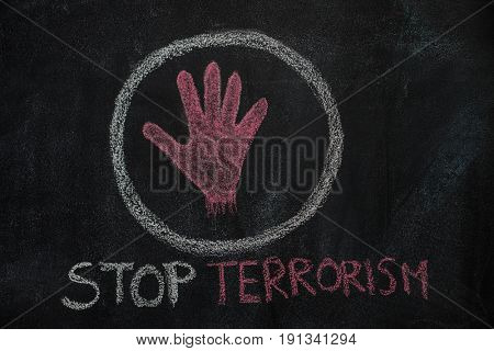 Hand shape and stop terrorism text in the circle drawn with red chalk on blackboard