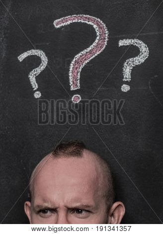 Closeup portrait of young man confused man isolated over black chalkboard with drawn question marks