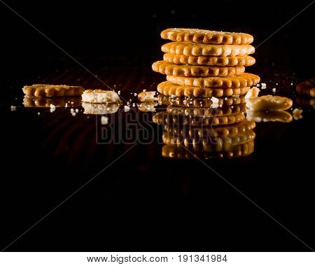 A stack of cookies and crumbs on a dark glossy background. Copy space.