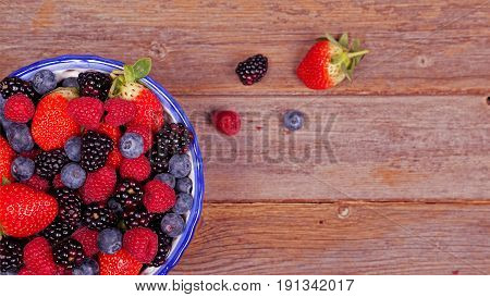 Mixed ripe sweet berries in a blue and white bowl with some berries that have spilt out of the bowl on a wooden backgrouond. Blueberries raspberries strawberries and blackberries. With space for text.