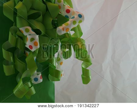 A couple of white ribbons with poke-a-dots amongst green ribbon attached to a green bag with lots of textured white space.