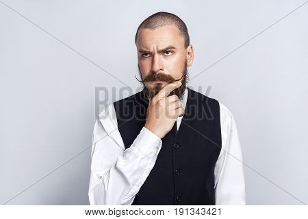 Thinking. Handsome businessman with beard and handlebar mustache looking and thinking. studio shot on gray background.