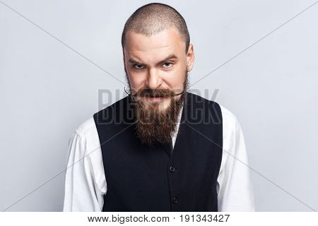 Angry. Handsome businessman with beard and handlebar mustache looking at camera with angry face. studio shot on gray background.