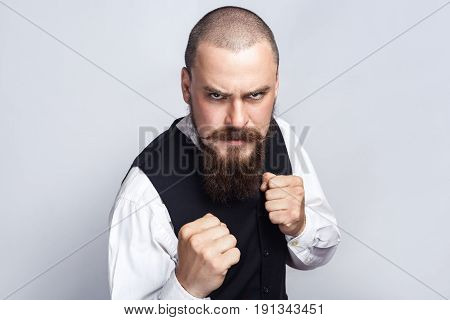 Angry boxing. Handsome businessman with beard and handlebar mustache looking at camera with angry face and fist. studio shot on gray background.