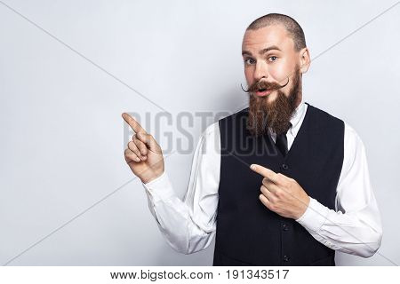 Handsome businessman with beard and handlebar mustache looking at camera surprised and showing copy space with fingers. studio shot on gray background.