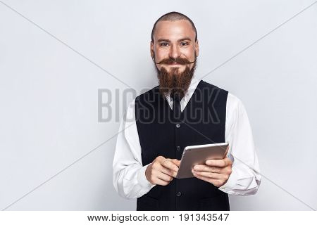 Handsome businessman with beard and handlebar mustache holding digital tablet and looking at camera with smiley face. studio shot on gray background.