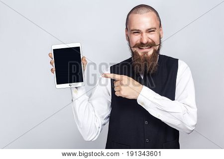 Handsome businessman with beard and handlebar mustache holding digital tablet and looking at camera and showing screen with finger and laughing. studio shot on gray background.