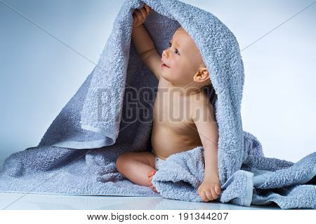 Eight month baby after washing sitting in big soft towel and smiling on white and blue background