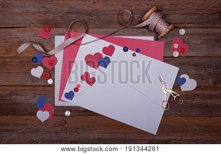 Selection of scrapbooking papers card shapes like hearts buttons ribbon on a bobbin and scissors on a wooden background with a vintage feel. With space for text.