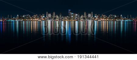 Fantastic nighttime panoramic city view with illuminated skyscrapers reflected on calm water. Ultra wide night time panoramic view of Seatle.