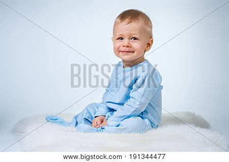 Eight month baby sitting on fur carpet on white and blue background