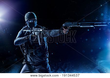 Strong man military special forces standing with guns on snow at night