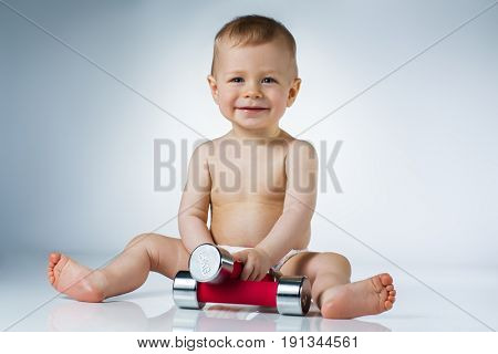 Eight month baby sitting with dumbbells and smiling on white background