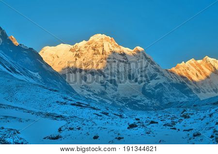 Sunrise in Snowy Mountain Landscape in Himalaya. Sun light. Annapurna South peak, Nepal, Annapurna Base Camp Track.