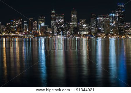 Fantastic nighttime panoramic city view with illuminated skyscrapers reflected on calm water. Nnight time panoramic view of Seatle.