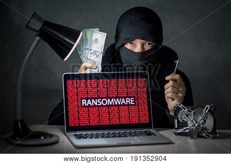 Hacker holding key and money with laptop computer screen showing ransomware attacking alert in red digital binary background with hard disk drive lock. Cyber attack concept