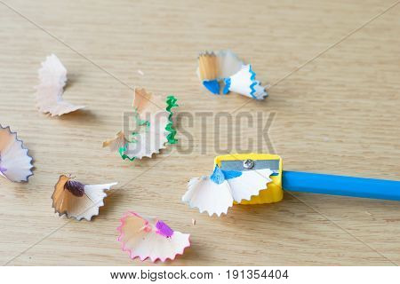 The Blue Color Pencil With Sharpener And Shavings On The Wood Table.