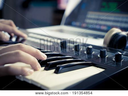 Music producer is working with Synthesizer and laptop