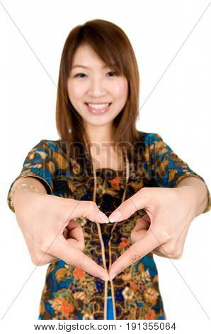 Southeast Asian girl wearing batik kebaya with hand forming a heart shape, standing isolated on white background.