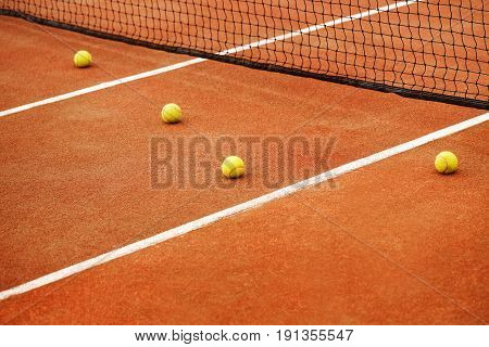 Four yellow tennis balls lie on the tennis court near the net. The concept of sport.