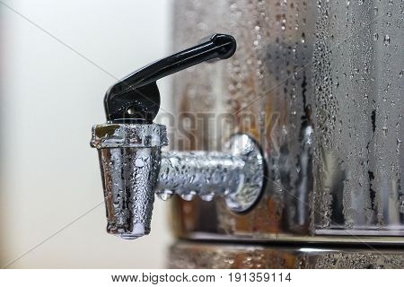 Faucet of cold drinking water steel tank with water drops.