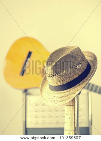 Straw hat on an electric vintage guitar in a studio