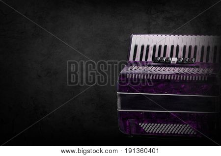 Part pink accordion on wooden grey background. Write text.